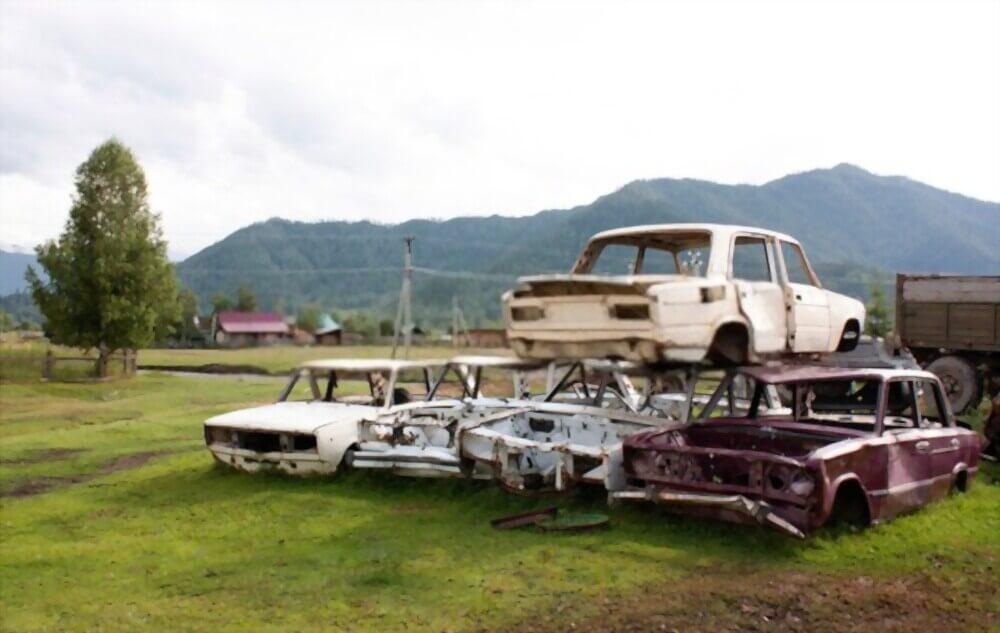 Autos sind in der Natur gestapelt - Autoverschrottung, Autoverwertung, Autoentsorgung deutschlandweit